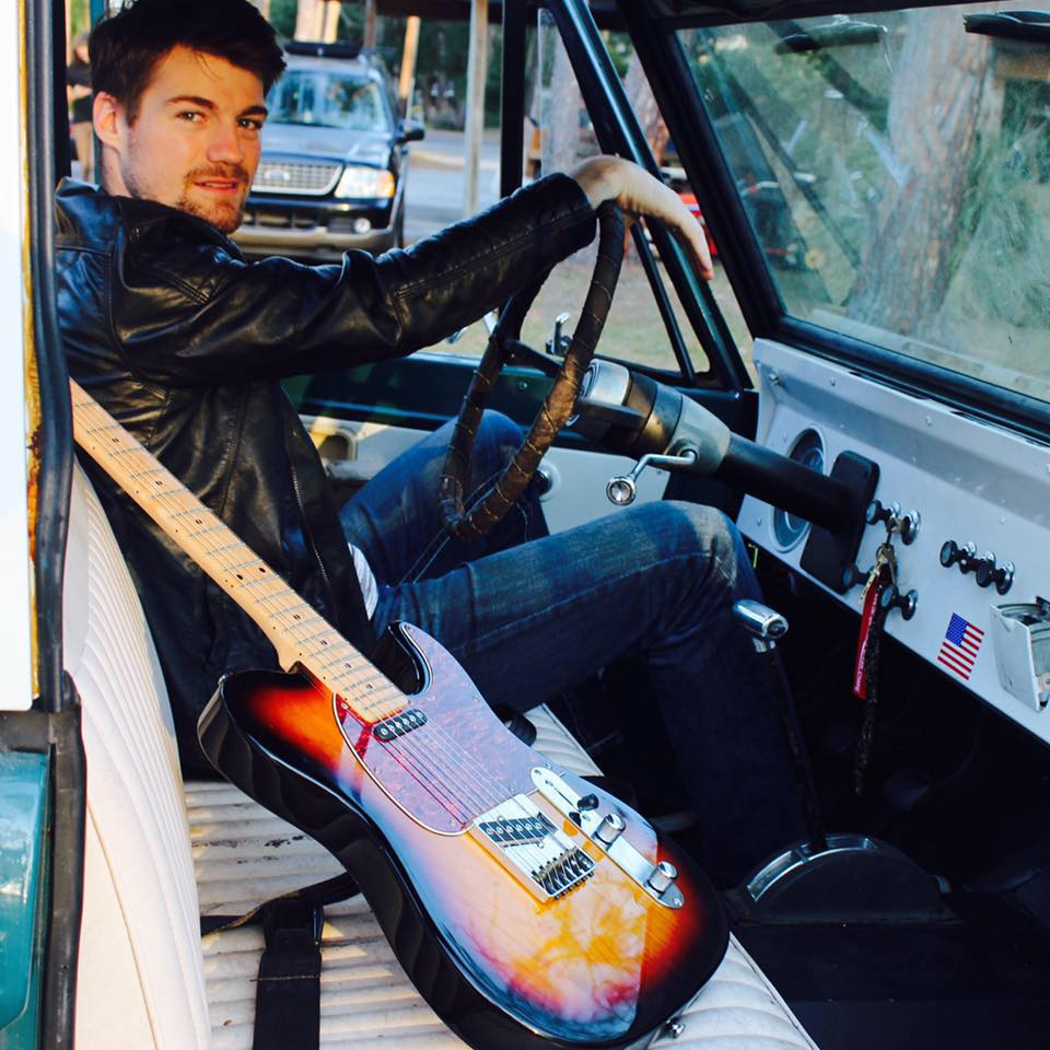 Justin Lee Partin in truck with a guitar